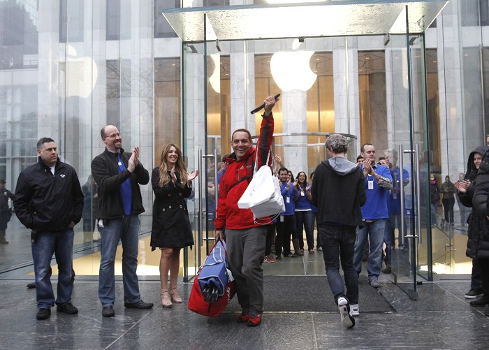 249346-a-man-raises-apples-new-ipad-after-purchasing-it-in-new-york L'iPad 3 fait le buzz à New York